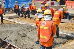 Konkrete strömende Arbeit während der concreting Böden der Straße Stockfoto