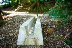 Konkrete Sturmregenentwässerung auf einem Fußweg im Wald Lizenzfreie Stockbilder