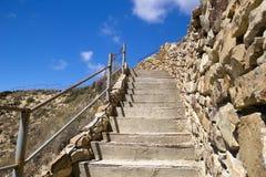 Konkrete Treppe bis zum Hügel und zum blauen Himmel Stockfotografie