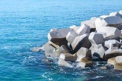 Konkrete Zahl Blöcke geworfen in das Meer Quay von Athen, Griechenland lizenzfreie stockbilder