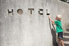 Konkrete Zaunwand, Hoteltext, junger blonder Junge Lizenzfreie Stockfotografie