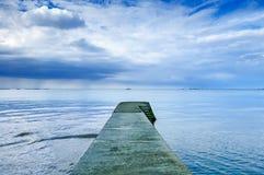 Konkreter Pier oder Anlegestelle auf einem blauen Meer und einem bewölkten Himmel. Normandie, Frankreich Lizenzfreie Stockbilder