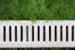 Konkreter Wasserabfluß oder -abzugsgraben auf der Straße mit grünem Gras Stockfotografie