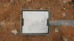 Konkretes Einsteigeloch auf dem Boden Stockfoto