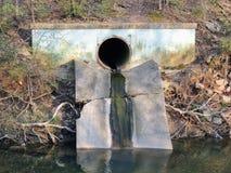 Konkretes Metallrohr oder -rohrleitung für das Abwasser, das zu Bean Creek durch Garfield Park mit dem Sonnenlicht nachdenkt über Stockfotografie