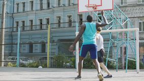 Konkurencyjni gracze koszykówki drybluje piłkę przy sądem, aktywny styl życia, bawją się zdjęcie wideo