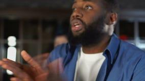 konkurrens för sportar för Afro--amerikan grabb hållande ögonen på i den hemtrevliga ölrestaurangen som slå vad stock video