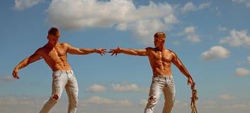 Konkurrens gör dem bättre Kopplar samman konkurrenter med muskulösa kroppar Män visar av deras styrka mot konkurrenter fotografering för bildbyråer