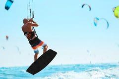 konkurrensar som dyker pölsportar som simmar vatten Kiteboarding Kitesurfing i havet extrem sport Arkivfoton
