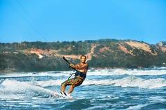 konkurrensar som dyker pölsportar som simmar vatten Kiteboarding Kitesurfing Surfare som surfar vågor A Royaltyfria Bilder
