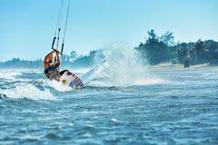 konkurrensar som dyker pölsportar som simmar vatten Kiteboarding Kitesurfing Surfare som surfar vågor A Arkivbilder