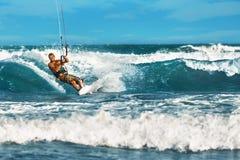 konkurrensar som dyker pölsportar som simmar vatten Kiteboarding Kitesurfing Surfare som surfar vågor A Royaltyfri Fotografi