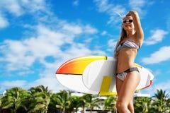konkurrensar som dyker pölsportar som simmar vatten surfa Kvinna med surfingbrädan på sommarferier Arkivfoto