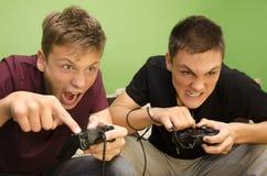 Konkurrenskraftiga bröder som spelar roliga videospel royaltyfria bilder