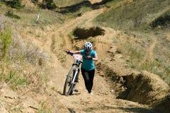 Konkurrent, der sein Fahrrad auf einem Hügel drückt stockbilder
