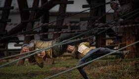 Konkurrenten, die von den Seilen bei Hindernisrennen 2014 des harten Jungen fallen Stockbild
