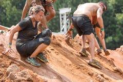 Konkurrenter glider ner den hala kullen på det extrema loppet för hinderkursen arkivfoto