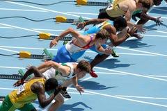 Konkurrenter på start av 110m manhäckar royaltyfri fotografi