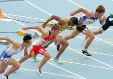 Konkurrenter på start av 110m manhäckar royaltyfri foto