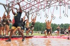 Konkurrentgunga från cirklar över vatten på det extrema loppet för hinderkurs Royaltyfri Fotografi