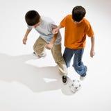 Konkurrenzfähiger Junge, der versucht, Fußballkugel zu nehmen Stockbilder