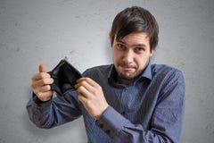 Konkurs- och obeståndbegrepp Den unga mannen har inga pengar och visar den tomma plånboken Royaltyfri Bild