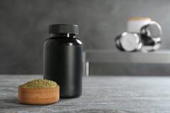Konopiany proteina proszek w pucharze i słoju na stole zdjęcia stock