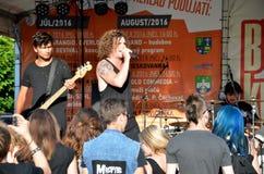 Konserten för öppen luft av vaggar musikmusikbandet som kallas det paranoid Gitarristen och sångaren står framme av gruppen av un royaltyfria foton
