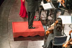 Konsertledarecloseup med musikmusikbandet i teatern arkivfoto