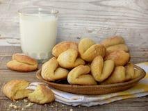 Konservera kakor i en korg, och ett exponeringsglas av mjölkar royaltyfria bilder