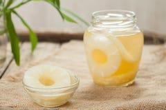 Konservierte Ananas kreist mit Saft im Glas auf Weinlesestoff ein Stockbild