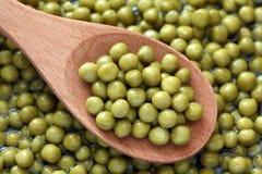 Konservierte grüne Erbsen in einem hölzernen Löffel Lizenzfreie Stockbilder