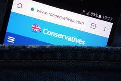 Konserwatysta partii politycznej strona internetowa wystawiająca na smartphone chującym w cajgach wkładać do kieszeni fotografia royalty free
