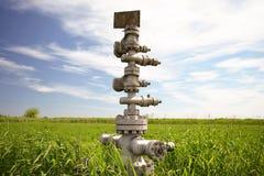 Konserwować szyb naftowy przeciw polu i niebu Fotografia Stock