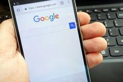 KONSKIE, ПОЛЬША - 6-ОЕ МАЯ 2018: Человек держа его smartphone с поиском Google Стоковое фото RF