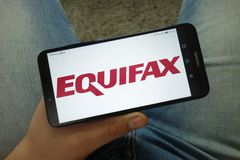 Man holding smartphone with Equifax Inc. company logo stock images