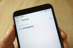 KONSKIE POLSKA, Maj, - 18, 2019: r?ki mienia smartphone z 911 nag?ego wypadku notatk? na notepad zastosowaniu fotografia royalty free