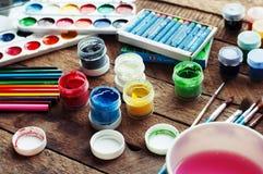 Konst av målning Målarfärghinkar på wood bakgrund Olik målarfärg färgar målning på träbakgrund Måla uppsättningen: borstar PA royaltyfri bild