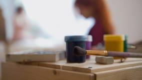 Konst levererar och målar framme av painer som utför den nakna modellen för konstnärlig etudewitn Fotografering för Bildbyråer