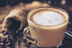 Konst och cappuccino för latte för kaffekopp med hjärta-format gjort från mjölkar på den wood tabellen med stekheta kaffebönor Dr arkivbilder