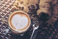Konst och cappuccino för latte för kaffekopp med hjärta-format gjort från mjölkar på den wood tabellen med stekheta kaffebönor Dr arkivfoto