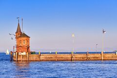 Konstanz, Germany - Stone dock with small tower at harbor of Lake Constance during sunset in summer