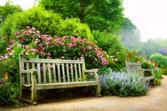 Konstbänken och blommor i morgonen i ett engelska parkerar arkivfoton