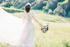 Konstbröllopfotografi Härlig brud med buketten och klänning med drevet i natur arkivbilder