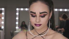 Konsten av makeupflickan med svarta ögonbryn arkivfilmer
