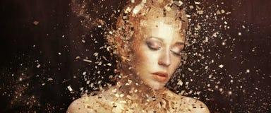 Konstfoto av den guld- kvinnan som splittrar till tusentals beståndsdelar Royaltyfri Bild