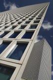 Konstfotoet förvridet i proportionen av en skyskrapavägg mot en bakgrund för blå himmel, den blåa himlen reflekteras i fönstret Arkivfoton