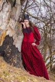 Konstfotografi Härlig felik prinsessa i röd klänning och spetsig svart krona i skog i tidig vår royaltyfri bild