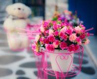 Konstgjord blomma i vase med den oskarpa dockan i   Arkivfoto