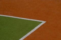 Konstgjord gräsplan och brun torvatexturbakgrund med den vita linjen fläckar arkivbild